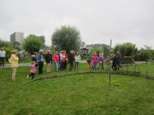 Ad liet de kinderen helpen bij het vlechten van een zonnewijzer van wilgetenen.